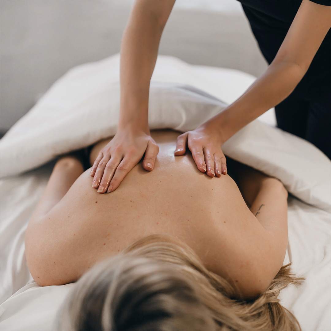A woman having a massage in one of the massage studios of the Spa William gray.