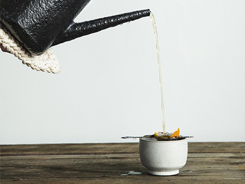 Une boisson chaude versée d'une théière dans une tasse posée sur une table en bois