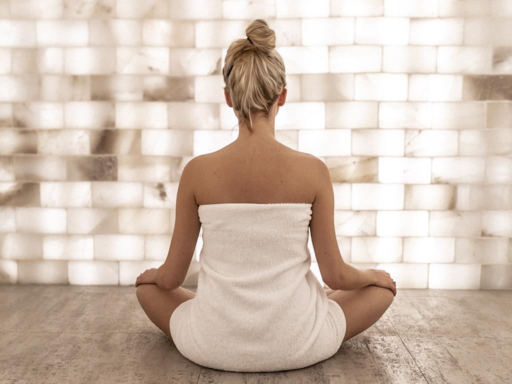 Une fille en serviette en train de méditer dans la chambre de sel du Spa William Gray