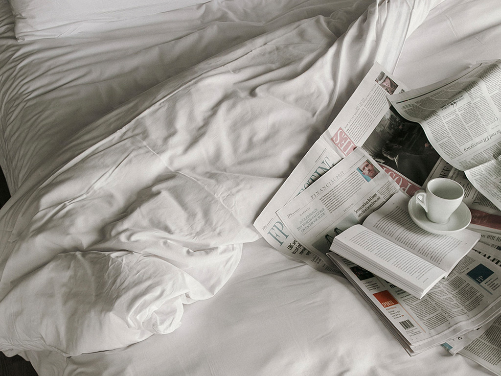 Book, newspapers and cup of coffee on an unmade bed