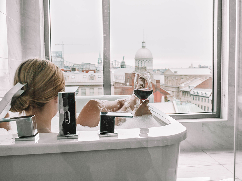 A girl in a bath drinking a glass of wine facing the Old Montreal view