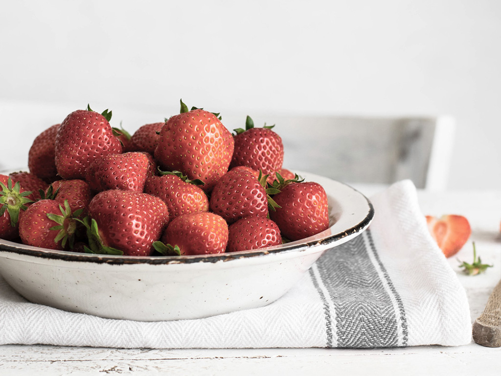 Une assiettes de fraises posée sur un linge