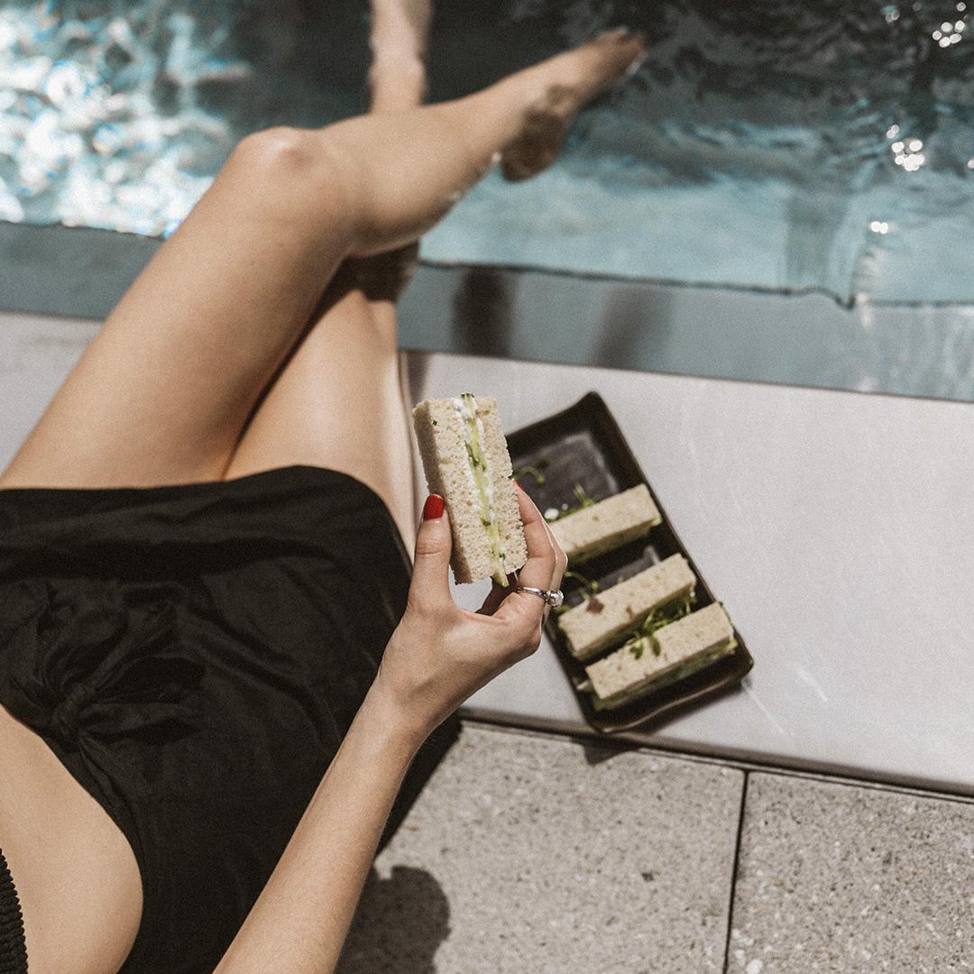 Une personne en train de manger un sandwich les pieds dans la piscine du Spa William Gray.