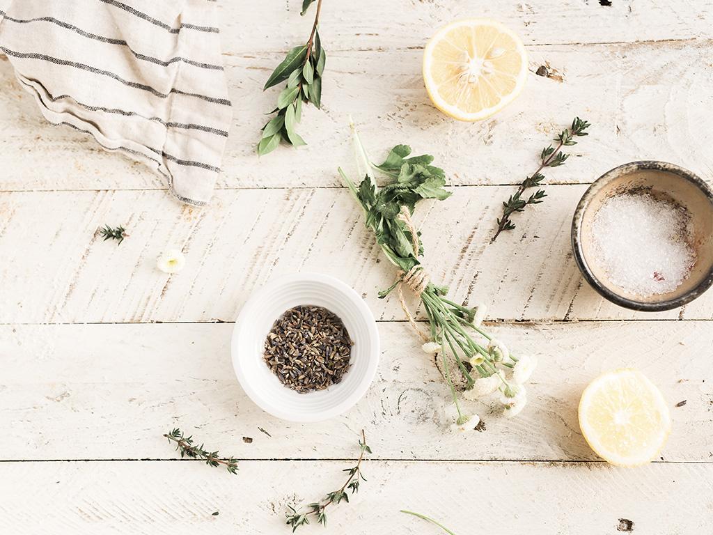 Des herbes et des citrons posés sur une table en bois